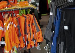 Arbeitskleidung und Warnschutzkleidung auf Ständern aufgehängt