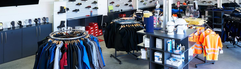 Ladengeschäft von Schunk Industriebedarf mit Arbeitskleidung auf Ständern, Sicherheitsschuhen im Wandregal und Arbeitshandschuhe auf Schrank