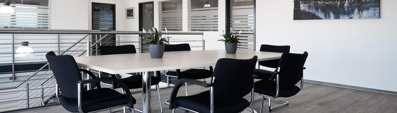 Konferenzraum mit großem Tisch und 6 Stühlen und 2 Blumentöpfen auf dem Tisch